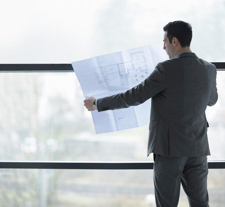 grays: Architect inspecting plans by office window