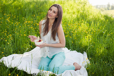 getting out: Woman in field of buttercups with a bowl of fresh fruit