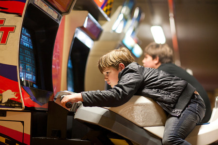 level playing field: Two young brothers playing on driving video games