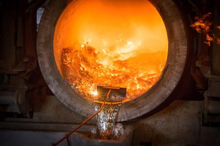 environmentalism: Raking liquid aluminum from furnace at recycling plant
