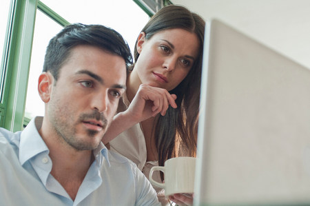 low self esteem: Young office workers looking at laptop