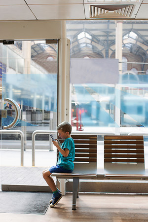 view through door: Young boy in train station waiting room playing electronic game