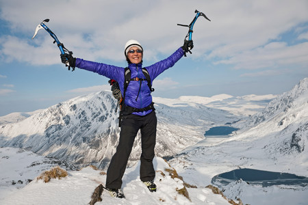 Female climber celebrating on top of snow covered peak