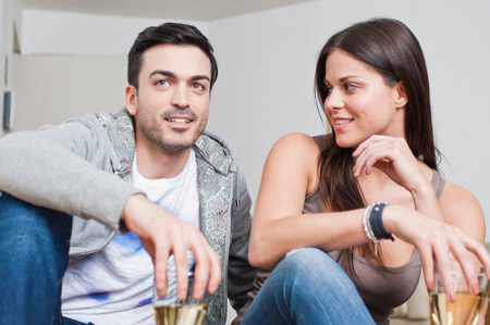sleeveless hoodie: Young couple sitting down sharing glass of wine