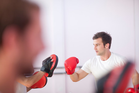 impulsive: Young man and trainer boxing in sports hall LANG_EVOIMAGES