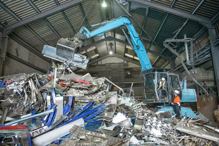 environmentalism: Workers and excavator lifting scrap metal in warehouse