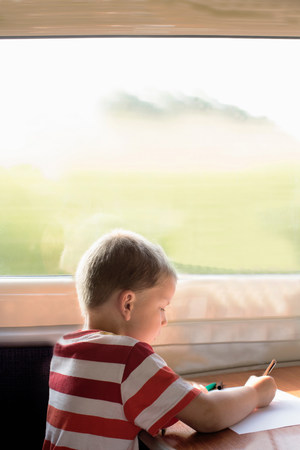 Young boy drawing on train LANG_EVOIMAGES