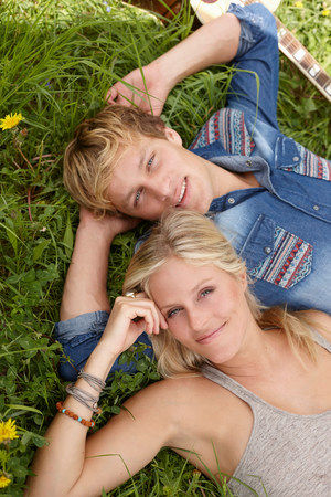 untruth: Young couple lying on grass looking at camera LANG_EVOIMAGES