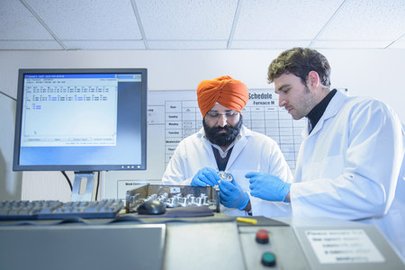 two persons only: Scientists checking quality of aluminum sample