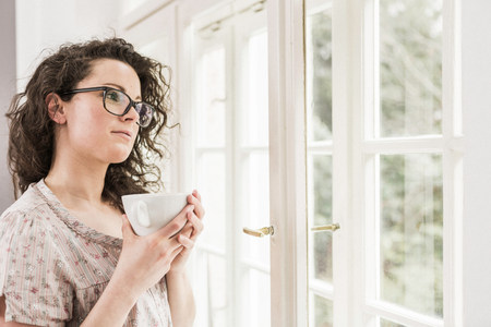 Mid adult woman holding coffee cup,looking out of window