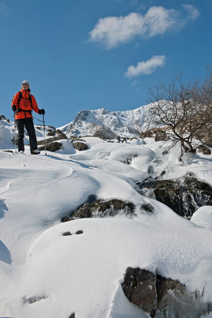 north western european descent: Female climber walking down snow covered mountain,Pen y Benglog,Snowdonia LANG_EVOIMAGES