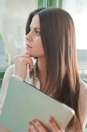 electronic organiser: Young woman in office looking out of window