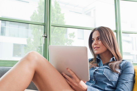 chillout: Young woman lounging on sofa holding digital tablet