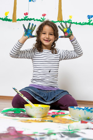 Girl kneeling on floor with painted hands