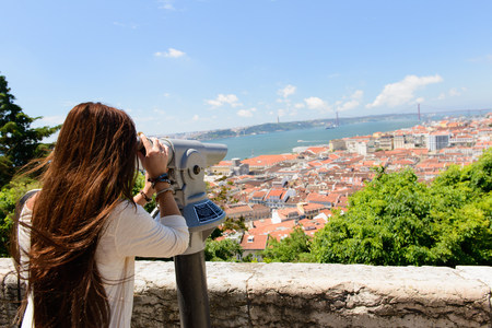 Young female tourist looking through coin operated binoculars in Lisbon,Portugal