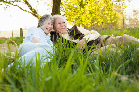living idyll: Senior couple relaxing and having picnic on field
