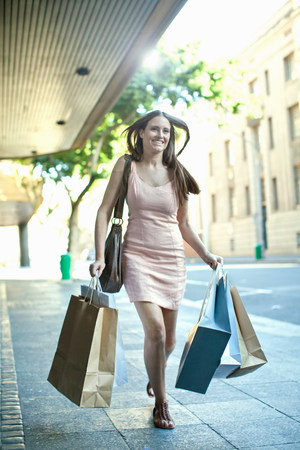 Young woman running with shopping bags