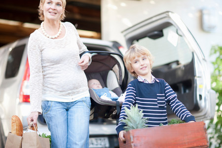 Mother with baby car seat and son carrying box of plants LANG_EVOIMAGES
