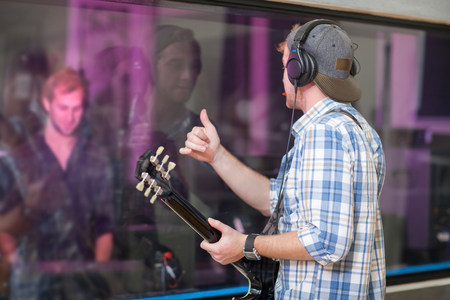 ear buds: Young guitarist in recording studio