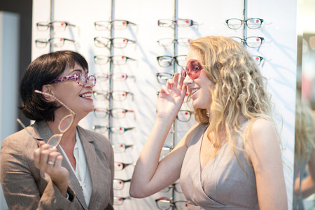 sight seeing: Two women trying on eyeglasses in opticians shop