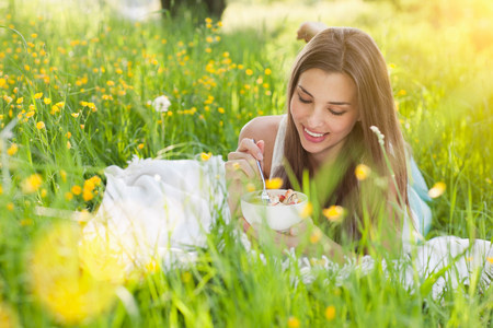 living idyll: Young woman in field of buttercups eating fresh fruit