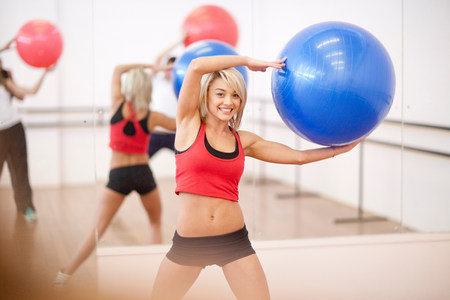 above 18: Young woman holding exercise ball in aerobics class LANG_EVOIMAGES