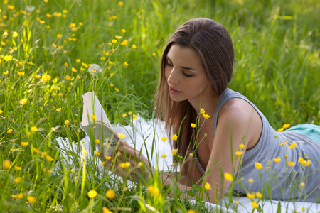 free education: Young woman reading in field of buttercups