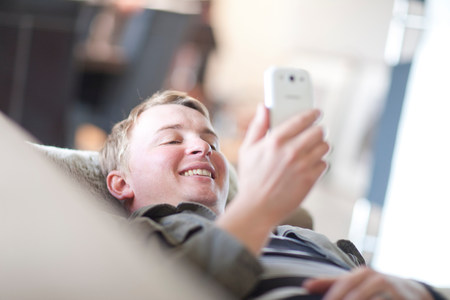 parlours: Man lounging on sofa looking at cellphone