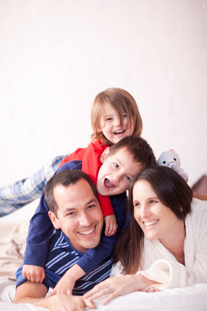 cropped out: Portrait of parents and two young children on bed LANG_EVOIMAGES