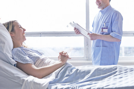 recuperating: Patient lying in hospital bed laughing with nurse