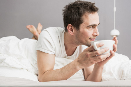 slacker: Mid adult man lying on front on bed,holding coffee cup