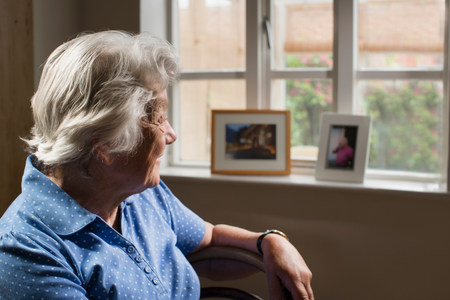 70 75: Senior adult woman sitting in room looking out of window