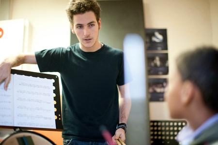通信: Young male teaching boy how to play drums LANG_EVOIMAGES