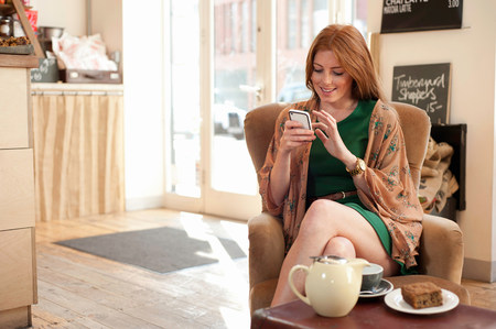 Portrait of young woman using smartphone in cafe