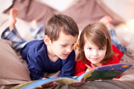 Two young children lying on bed looking at picture book LANG_EVOIMAGES