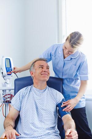 recuperating: Nurse taking patients blood pressure