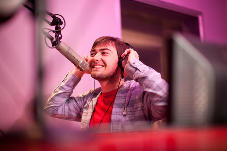 purples: Young man broadcasting in recording studio,smiling LANG_EVOIMAGES