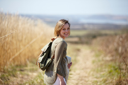 Portrait of young woman on dirt track next to field of reeds