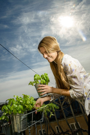 Young woman holding pot plant
