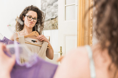 coathangers: Mid adult woman holding up dress in front of mirror LANG_EVOIMAGES