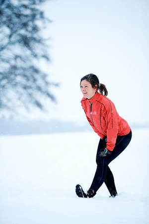 wintry weather: Woman stretching before snow run LANG_EVOIMAGES