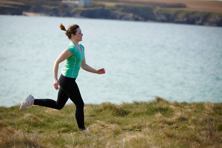 run way: Young woman running near coast