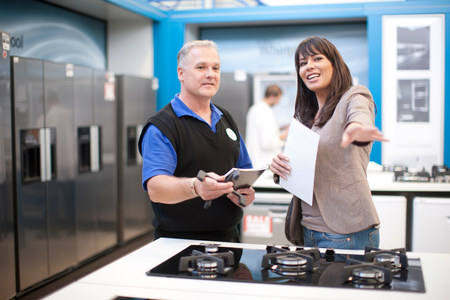 Woman and kitchen appliance salesman in showroom