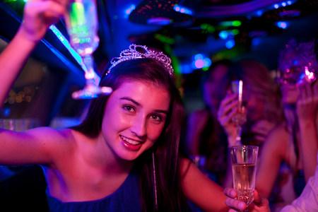 Mujer joven, llevando, tiara, con, copa de vino, en, limusina LANG_EVOIMAGES