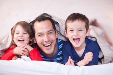 untruth: Father and two young children posing under duvet