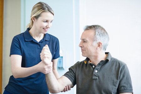 recuperating: Physiotherapist helping man to do arm exercise