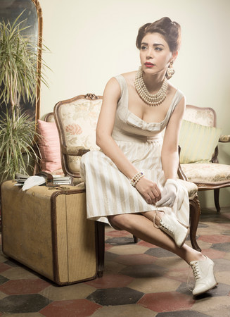 Woman in vintage clothes waiting in lobby with suitcase LANG_EVOIMAGES