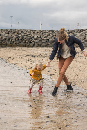 trouble free: Mother and toddler walking at waters edge
