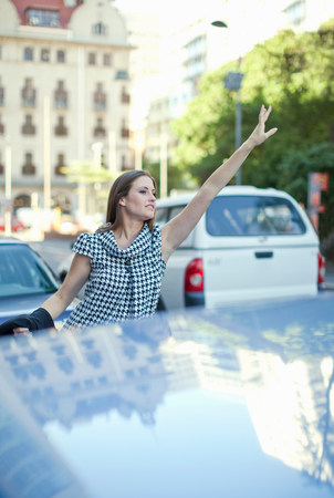 Young woman hailing a cab in Cape Town,South Africa