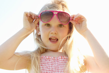 narcissist: Child putting on sun glasses on hot sunny day